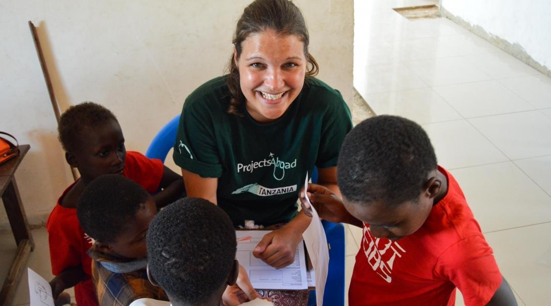 Interna de enfermería en Tanzania revisando pequeños pacientes.